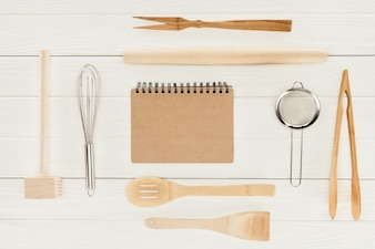 Top view of textbook and kitchen utensils on wooden white table