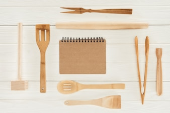 Top view of textbook and wooden kitchen utensils on white table