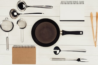 Top view of textbooks, frying pan and kitchen utensils on white wooden table