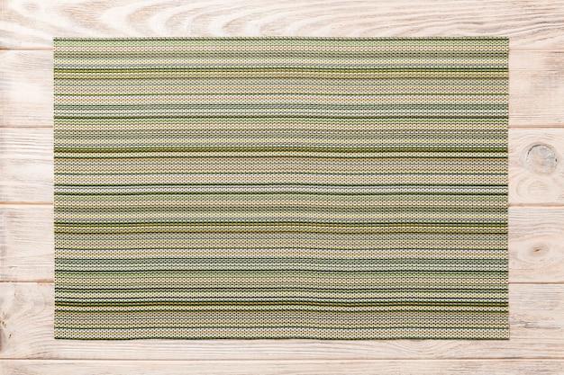 Взгляд сверху текстильной зеленой циновки для обеда на деревянной предпосылке с космосом экземпляра