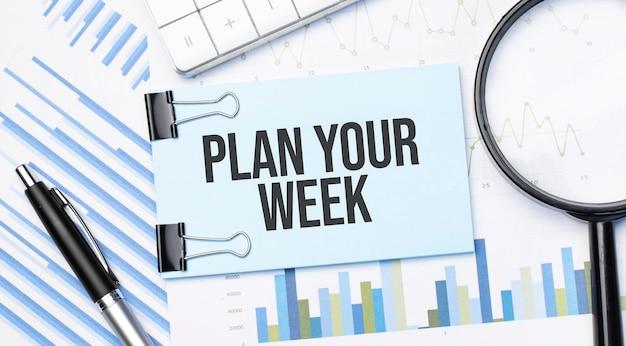 Вид сверху текста: спланируйте неделю с помощью калькулятора, увеличительного стекла и ручки на финансовых диаграммах. бизнес, расчет, стратегия, поиск и налоговая концепция. вид сверху.