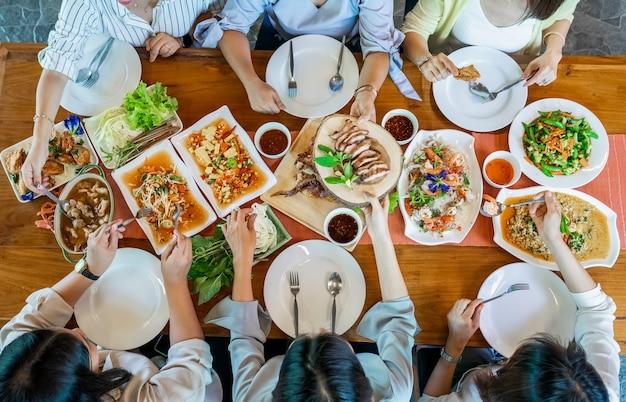 ソムタムパパイヤのスパイシーサラダ、ポークのグリル、トムヤムクン、野菜、エビのカレーなどのタイの郷土料理の平面図が木製のテーブルに並べられています。