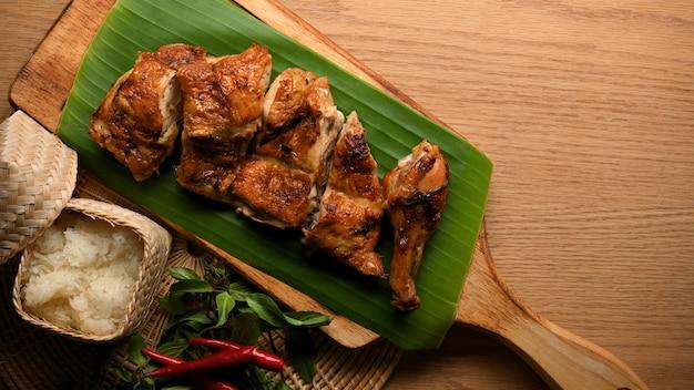 タイ風グリルチキンの上面図ともち米と木製トレイタイ料理