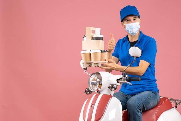 スクーターに座って帽子をかぶったマスクを着た感謝の男性配達員のトップビューで、桃にジェスチャーをして注文を配達