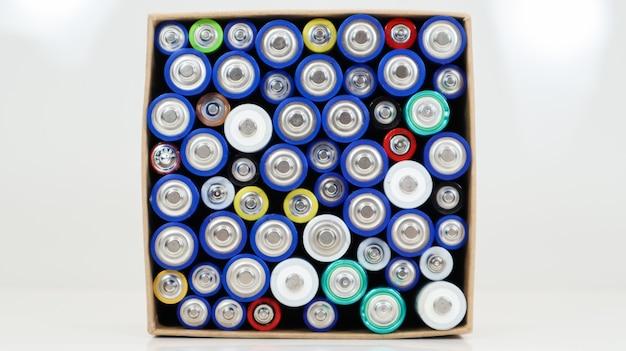 Вид сверху на фон батарей aaa aa и аккумуляторов. выбор батарей. концепция энергоснабжения и утилизации. текстуры электрических элементов плотно упакованы в коробку.