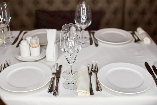 Вид сверху красиво украшенный стол с белыми тарелками хрустальные бокалы льняная салфетка
