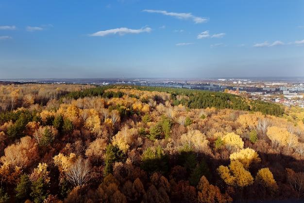 Вид сверху на город и осенний красочный лес