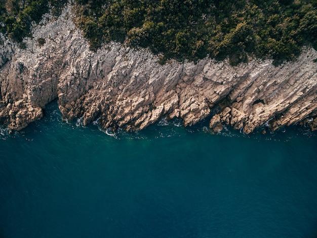 崖のターコイズブルーの水の岩の泡の波と木々のある海岸線の上面図