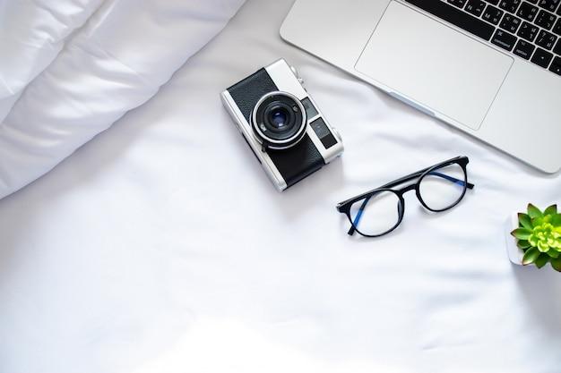 コンピューター、フィルムカメラ、部屋の白いベッドの上の眼鏡の平面図
