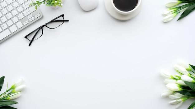 メガネとキーボードを備えたクリエイティブワークスペースの上面図。デスクホワイト。 Premium写真