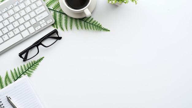 안경과 키보드가있는 창의적인 작업 공간의 상위 뷰. 책상 흰색.