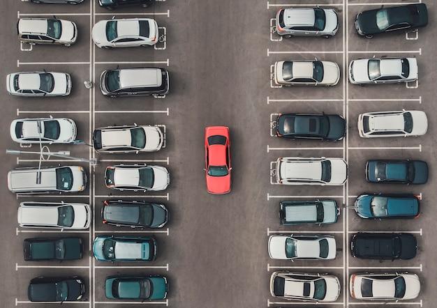 クワッドコプターまたはドローンのある混雑した駐車場の上面図。平凡な車の灰色の中でオリジナルの明るい自動車。駐車スペース検索、駐車スペースなし。