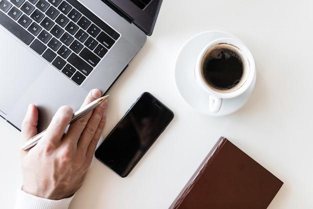 커피 한 잔, 노트북 및 기록 용 노트북이있는 데스크탑의 윗면보기