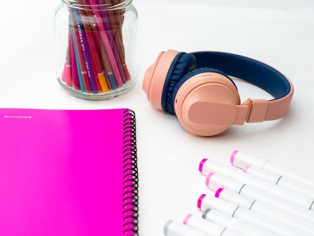 Вид на рабочий стол сверху. профессиональные разноцветные маркеры, розовая папка, наушники.