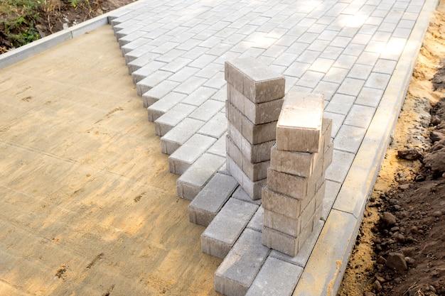 Вид сверху на край поверхности с уложенной серой тротуарной плиткой и поверхность с песчаной смесью