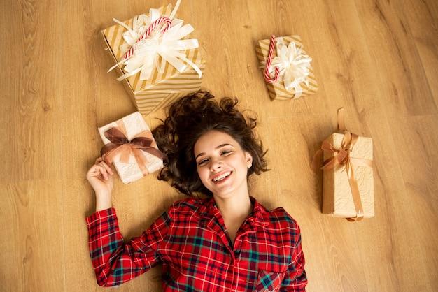 女の子の上面図。彼女はプレゼントを持って床に横たわっていた。クリスマス。新年