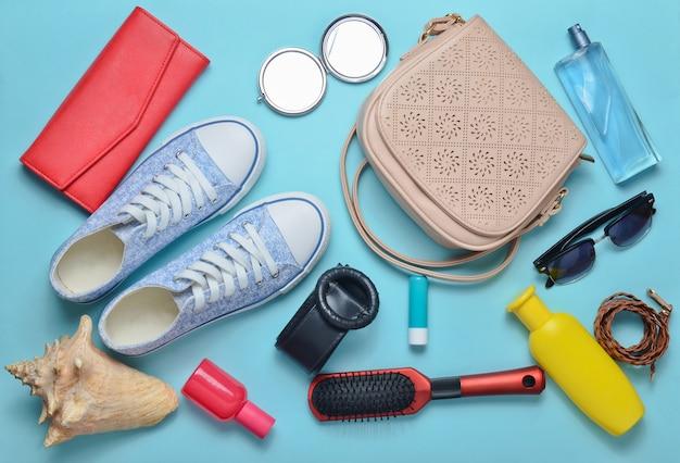 소녀의 봄 여름 액세서리의 상위 뷰 : 운동화, 화장품, 미용 및 위생 제품, 가방, 블루 파스텔 배경에 선글라스. 여행을 가다.