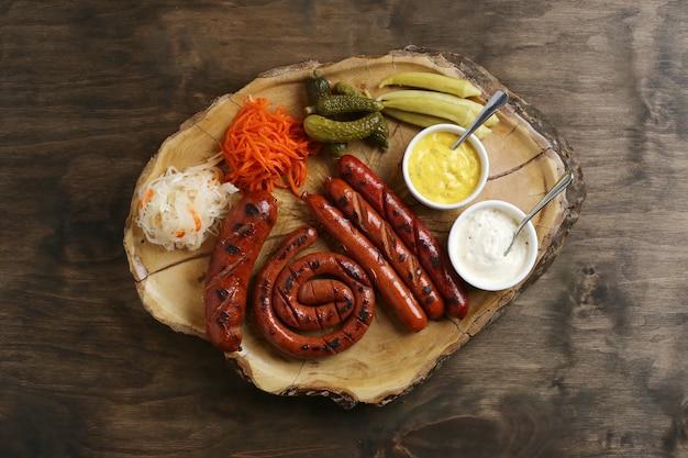 Вид сверху на колбаски-гриль с гарнирами и соусами