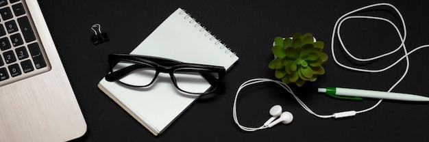 검정색 배경에 있는 노트북, 안경, 노트북, 헤드폰 및 녹색 식물의 위쪽 전망. 비즈니스, 프리랜서, 원격 작업 또는 사무실에서 일하는 개념. 배너.