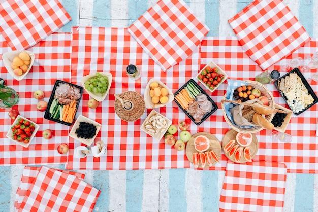 푸른 잔디에 있는 공원에서 점심의 최고 전망. 격자 무늬 천에 서있는 접시와 음료. 여름 화창한 날과 신선한 공기에서 피크닉