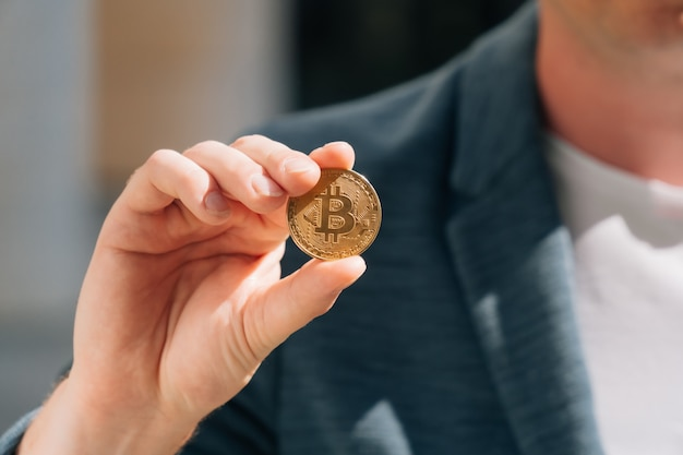 Вид сверху на мужские руки европейского бизнесмена, держащего в руках виртуальные монеты