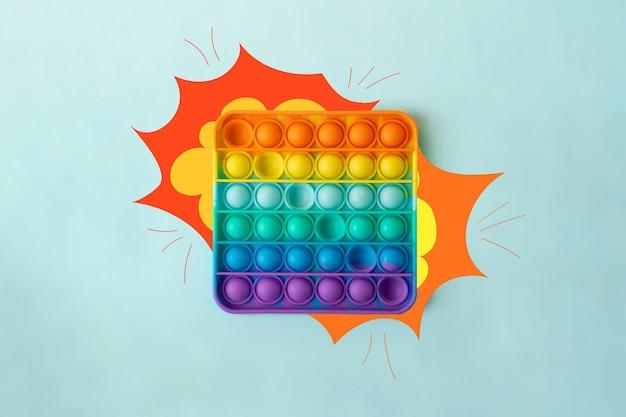 Вид сверху на новую сенсорную игрушку - радужный лопнет ее с нарисованным взрывом по бокам, похожим на звук, который она издает. игрушка-антистресс для детей и взрослых. разноцветная игрушка.