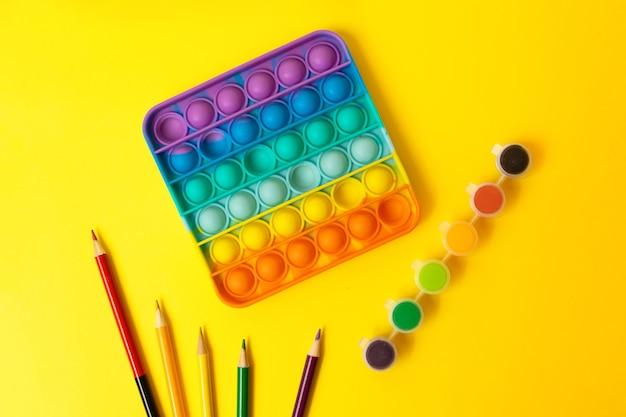 Вид сверху на новую сенсорную игрушку rainbow pop it с детскими предметами по бокам