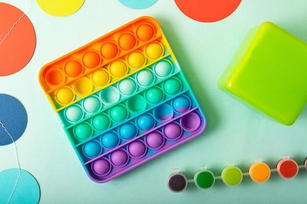 Вид сверху на новую сенсорную игрушку rainbow pop it с детскими игрушками по бокам
