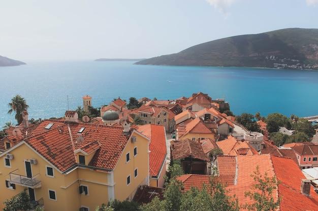 紺碧の海と美しい山々を背景にした家々のオレンジ色の瓦屋根の上面図。モンテネグロの写真。旅行のコンセプト。