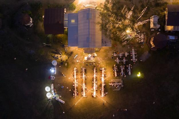 Вид сверху на вечеринку с обеденным столом и людьми в свадебном торжестве ночью