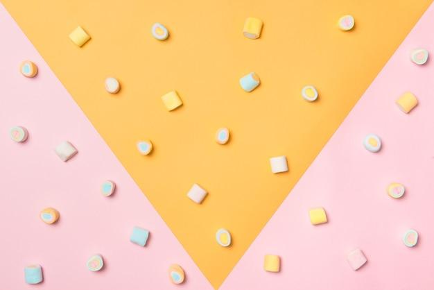 ピンクと黄色の背景にパステルマシュマロの上面図。ミニマルなスタイル。