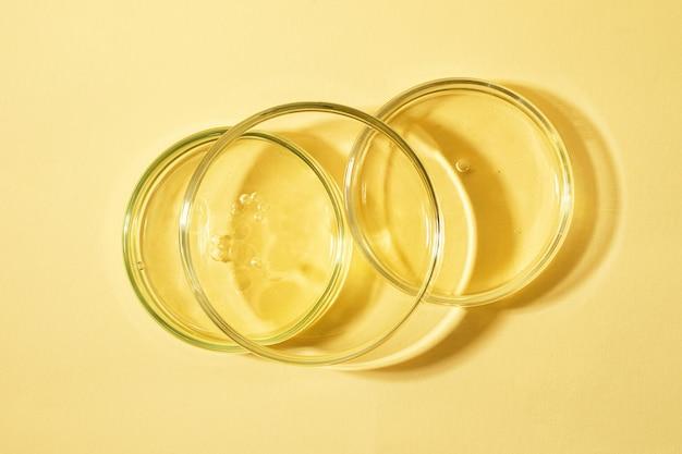 내부에 거품과 함께 서로 머물고 있는 페트리 접시의 상단 보기따뜻한 노란색 배경