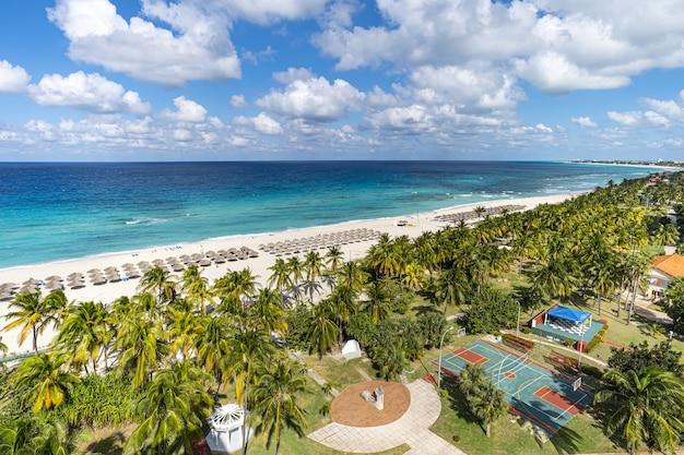 Вид сверху на курортный городок варадеро. куба. длинный пляж с шезлонгами, соломенными зонтиками и множеством пальм находится в 20 км.