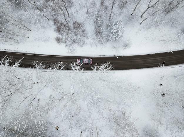 Вид сверху на дорогу через заснеженный лес, по которому едет машина