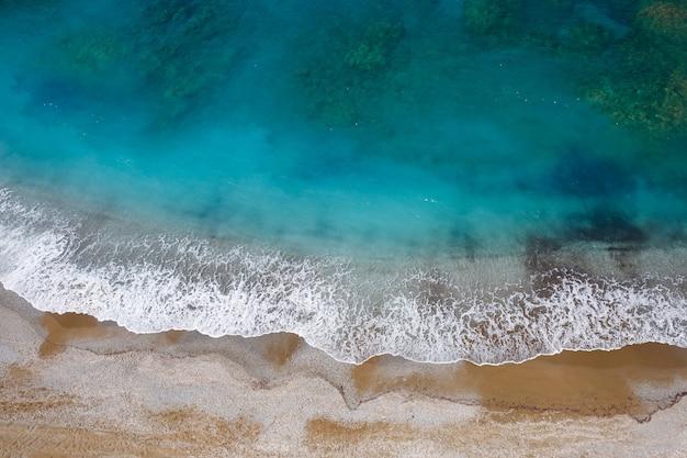 Вид сверху на морское побережье с лазурной водой и песчаный пляж. аэрофотоснимок средиземного моря с береговой линией. красивое море в летний сезон, снято с дрона