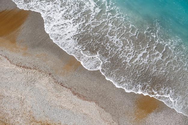 Вид сверху на морской берег с лазурной водой и песчаный пляж. вид с воздуха на средиземное море с береговой линией. красивое тропическое море в летний сезон, снято с дрона