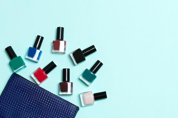 파란색 표면에 복사 공간이있는 화장품 가방에서 떨어진 매니큐어 및 밝은 젤 바니시 세트의 상위 뷰