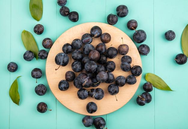青色の背景に木製キッチンボード上の小さな酸っぱい黒っぽい果物のスローのトップビュー