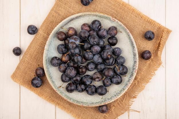 白い木製の背景に袋の布の上のボウルに小さな酸っぱい青黒果実のスローのトップビュー