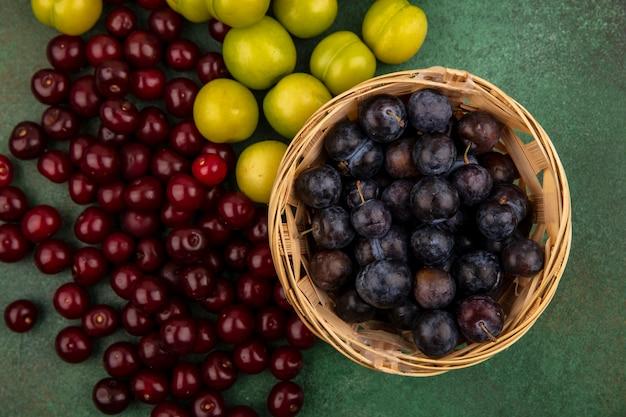 緑の背景に分離された新鮮な緑のチェリープラムと赤いサクランボのバケツに小さな酸っぱい青黒果実のスローのトップビュー