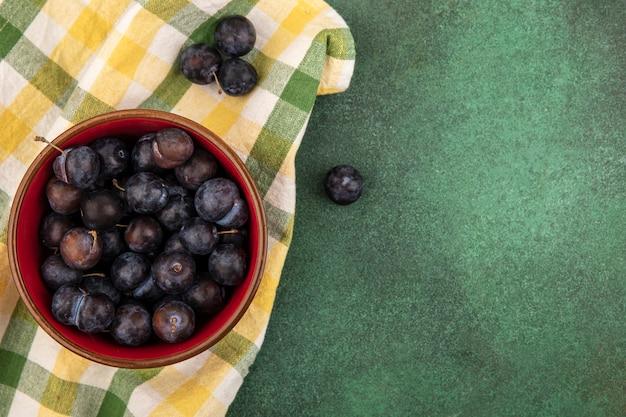 コピースペースと緑の背景のチェックのテーブルクロスに小さな酸っぱい青黒果実のスローのトップビュー