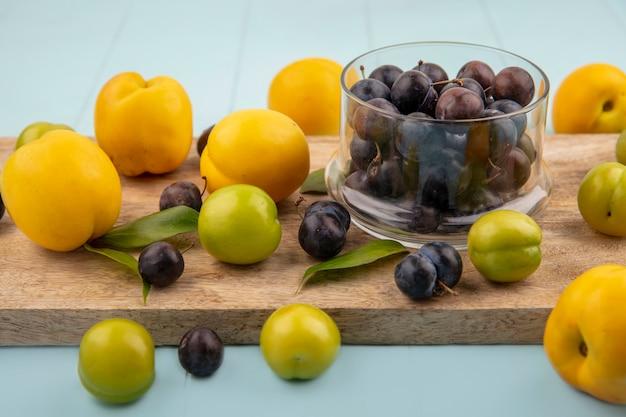 Вид сверху небольших кислых сине-черных ягод на стеклянной миске на деревянной кухонной доске с зелеными алычами с желтыми персиками на синем фоне