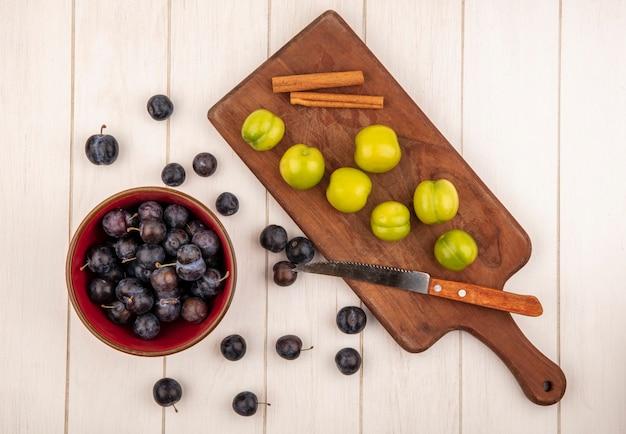 Вид сверху небольших кислых сине-черных ягод на красной миске с зеленой алычой на деревянной кухонной доске с палочками корицы с ножом на белом деревянном фоне
