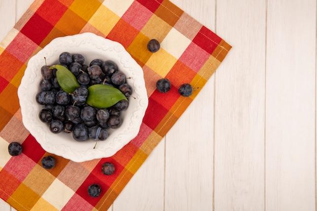 白地にカラフルなチェックのテーブルクロスに白いボウルに小さな酸っぱい青黒果物スローのトップビュー