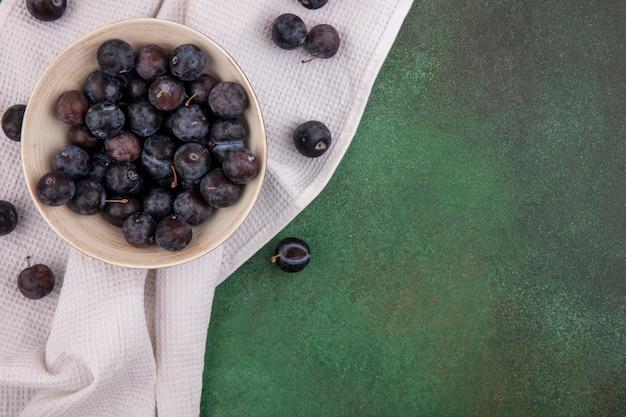コピースペースを持つ緑の背景のテーブルクロスの上の白いボウルに小さな酸っぱい青黒果物スローのトップビュー