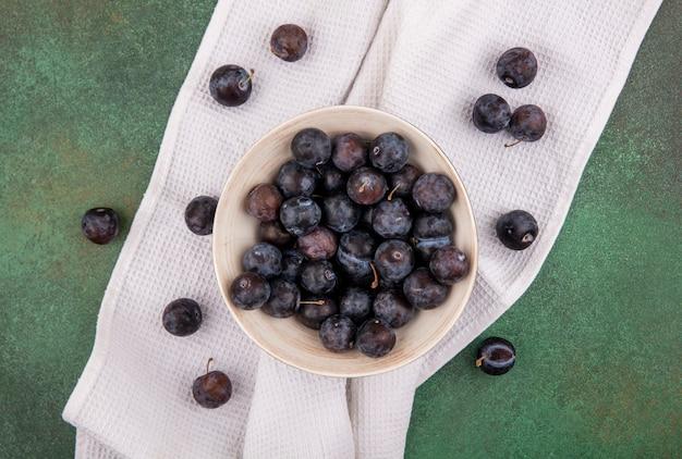 緑の背景にテーブルクロスの上の白いボウルに小さな酸っぱい青黒果物スローのトップビュー