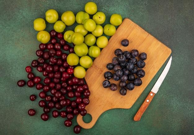 緑の背景に分離された赤いサクランボと緑のチェリープラムとナイフで木製キッチンボード上の小さな酸っぱい青黒果実のスローのトップビュー