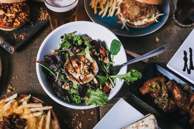 木製のテーブルにさまざまな料理、ハンバーガー、フライドポテト、サラダをテーブルの上から見る。レストランのメニュー。