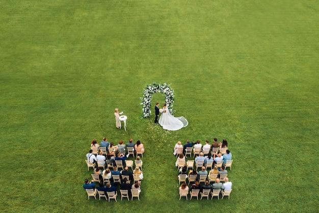 Вид сверху на свадебную церемонию в зеленом поле с гостями, сидящими на стульях