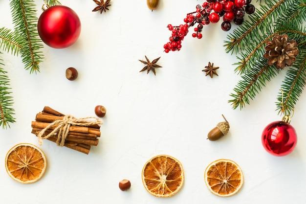 가문비나무 가지, 자그다, 빨간 공, 오렌지 슬라임, 계피, 아니스 별이 있는 흰색 크리스마스 배경의 최고 전망. 평면 레이아웃.